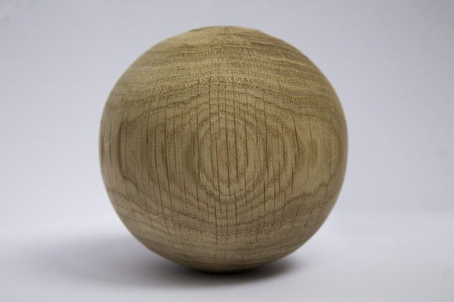A cracked carved wooden ball